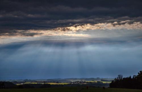 Abendsonne aus dunklem Himmel über oberbayrischem Dorf 22.06.2021